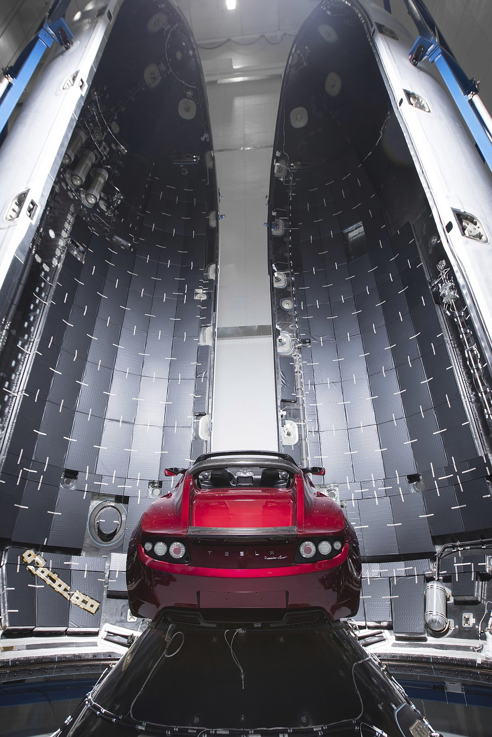 This Dec. 6, 2017 photo made available by SpaceX shows a Tesla car next to the fairing of a Falcon Heavy rocket in Cape Canaveral, Fla. For the Heavy's inaugural flight, the rocket will carry up Elon Musk's roadster. In addition to SpaceX, Musk runs the electric car maker Tesla. .(SpaceX via AP)