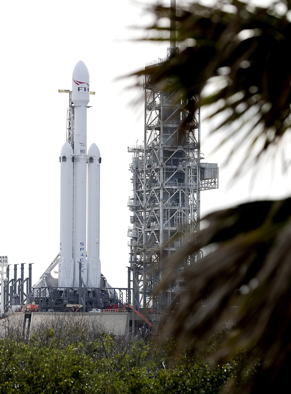 A Falcon 9 SpaceX heavy rocket stands ready for launch on pad 39A at the Kennedy Space Center in Cape Canaveral, Fla., Monday, Feb. 5, 2018. The Falcon Heavy, scheduled to launch Tuesday afternoon, has three first-stage boosters, strapped together with 27 engines in all. (AP Photo/John Raoux)