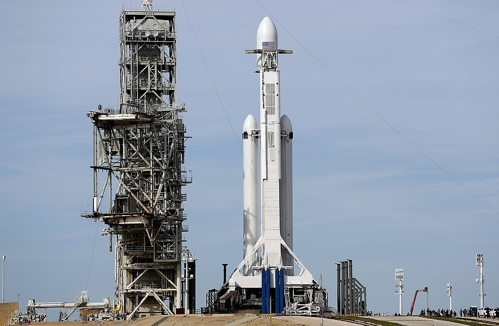 A Falcon 9 SpaceX heavy rocket stands ready for launch on pad 39A at the Kennedy Space Center in Cape Canaveral, Fla., Monday, Feb. 5, 2018. The Falcon Heavy scheduled to launch Tuesday afternoon, has three first-stage boosters, strapped together with 27 engines in all. (AP Photo/Terry Renna)