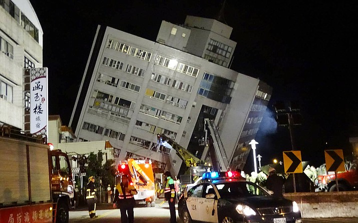 In this photo released by Hualien County Fire Bureau, rescuers are seen entering an building that collapsed onto its side from an early morning earthquake in Hualien County, eastern Taiwan, Wednesday, Feb. 7 2018. A 6.4-magnitude earthquake has struck eastern Taiwan, according to the U.S. Geological Survey. (Hualien County Fire Bureau)