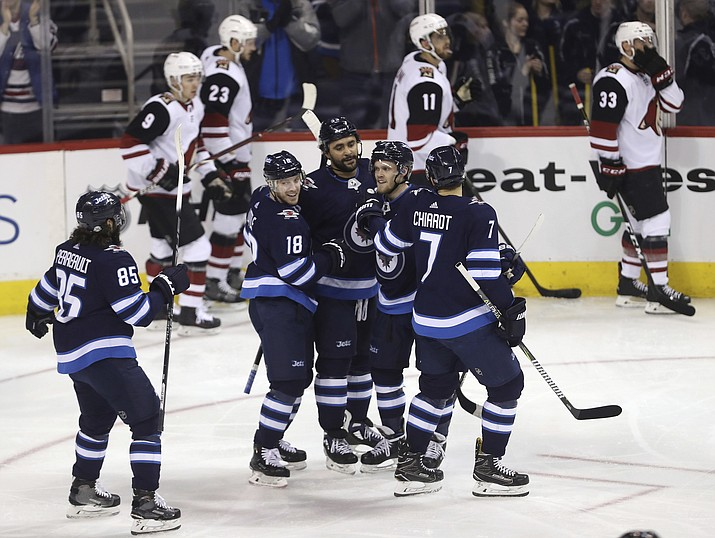 Winnipeg Jets' Mathieu Perreault (85), Bryan Little (18), Dustin Byfuglien (33), Nikolaj Ehlers (27) and Ben Chiarot (7) celebrate after Byfuglien scored against the Arizona Coyotes' during first period NHL hockey action in Winnipeg, Manitoba Tuesday, Feb. 6, 2018. (Trevor Hagan/The Canadian Press, via AP)