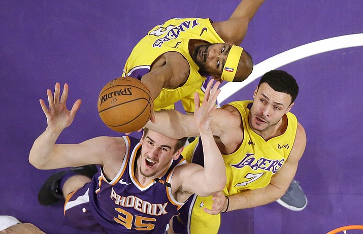 Phoenix Suns forward Dragan Bender, lower left, of Croatia, reaches for a rebound along with Los Angeles Lakers forward Corey Brewer, top, and forward Larry Nance Jr. during the first half Tuesday, Feb. 6, 2018, in Los Angeles. (Mark J. Terrill/AP)