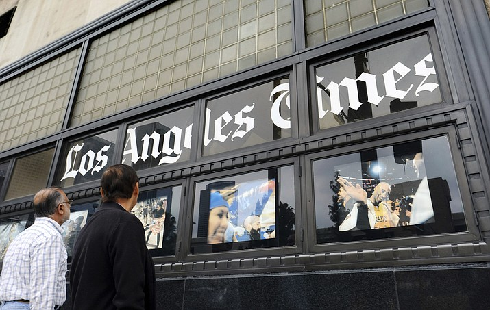 n this May 16, 2016, file photo, pedestrians look at news photos posted outside the Los Angeles Times building in downtown Los Angeles. It was announced Wednesday, Feb. 7, 2018, that the Los Angeles Times is being sold to Dr. Patrick Soon-Shiong, a local billionaire, for $500 million, ending its strained tenure under the owner of the Chicago Tribune. Soon-Shiong is a major shareholder of Chicago's Tronc Inc., one of the richest men in Los Angeles and, according to Forbes, the nation's wealthiest doctor, with a net worth of $7.8 billion. (AP Photo/Richard Vogel, File)