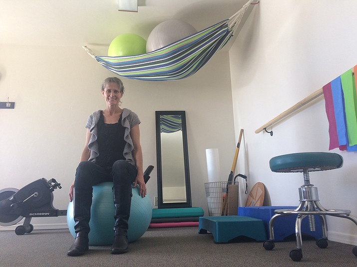 Leslie Terrell sits on a medicine ball in her newly opened business, Beyond Physical Therapy. (Jason Wheeler/Review)