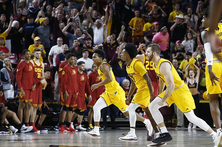 Arizona State's Mickey Mitchell, right, Shannon Evans II, middle, and guard Tra Holder, left, celebrate as time expires Thursday, Feb. 8, 2018, in Tempe. Arizona State defeated Southern California 80-78. (Ross D. Franklin/AP)