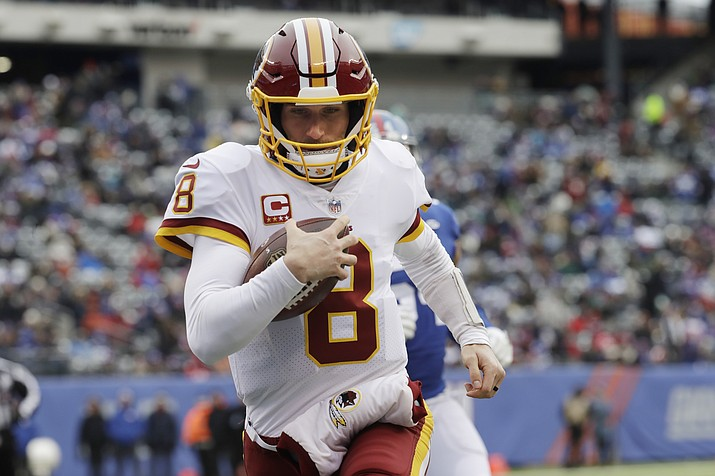 In this Dec. 31, 2017, file photo, Washington Redskins quarterback Kirk Cousins (8) rushes for a touchdown during the first half of an NFL football game against the New York Giants in East Rutherford, N.J. The quarterback carousel began in the days before the Super Bowl when Kansas City agreed to trade Alex Smith to the Redskins. The deal, which cannot be finalized until March 14, spells the end of Cousins' time in Washington and hands the Chiefs' job to Patrick Mahomes III, the 10th pick in last year's draft out of Texas Tech. (Mark Lennihan/AP, File)