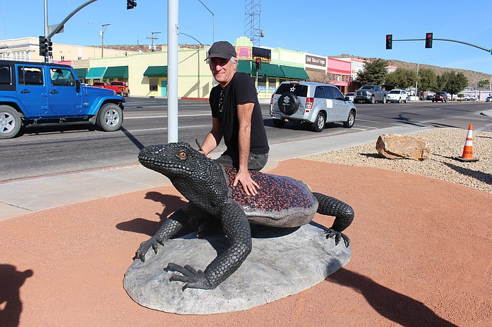 Artist Solomon Bassoff of Faducci Studio in North San Juan, California, sits on his Arizona chuckwalla lizard sculpture that was unveiled Friday. It's part of the City of Kingman's Art in Public Places program.