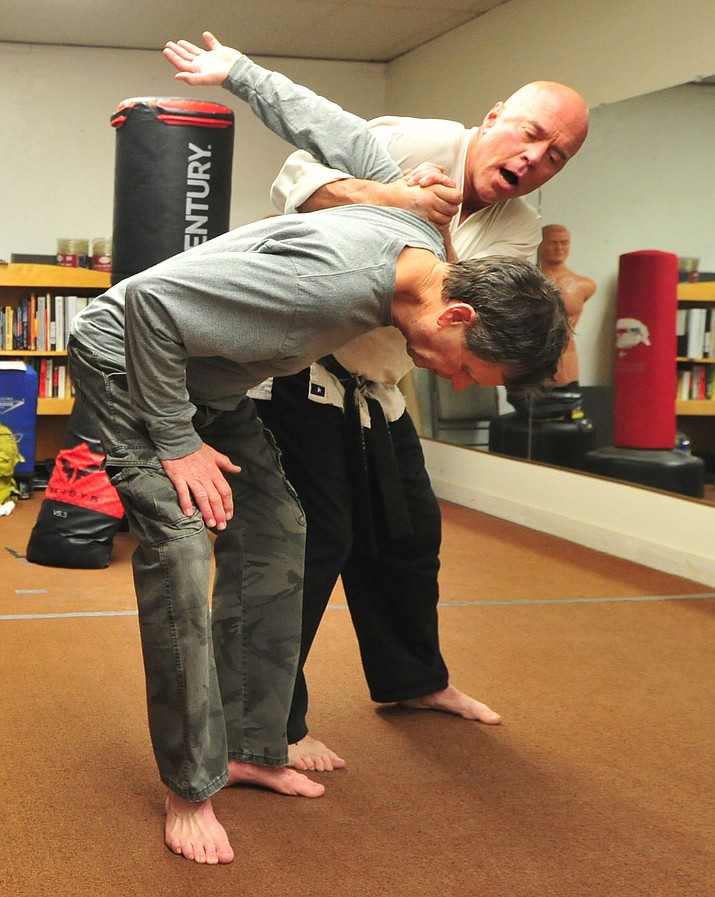 Real World Self Defense's Mark Bryans, at right, works with client Mike Russell before class on Thursday at Champions Gym in Prescott.  (Les Stukenberg/Courier)