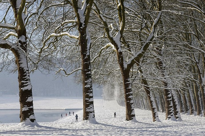 People stroll in the snow covered park of the Chateau de Versailles, west of Paris, Thursday, Feb. 8, 2018. Heavy snowfall has caused travel disruptions in the northern half of France and in Paris as the weather conditions caught authorities off guard. Due to the weather conditions, the Park and the Gardens were closed in the morning and reopened early afternoon Thursday. (AP Photo/Michel Euler)