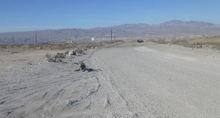 This photo shows the area facing west along the proposed project. Water tanks seen in KOP 1 photos are in the center and various Bullhead City buildings can be seen. Current power poles and wires are visible in the foreground. Newberry Mountains are in the background. (Photo from BLM report)