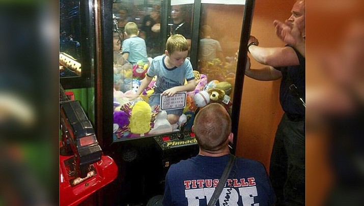 This photo made available by the Titusville Fire and Emergency services shows fire fighters attempting to rescue a boy who crawled inside a claw-style vending machine, Wednesday, Feb. 7, 2018, in Titusville, Fla. The boy sat atop the stuffed toys while firefighters took just 5 minutes to get him out. (Titusville Fire and Emergency Services via AP)