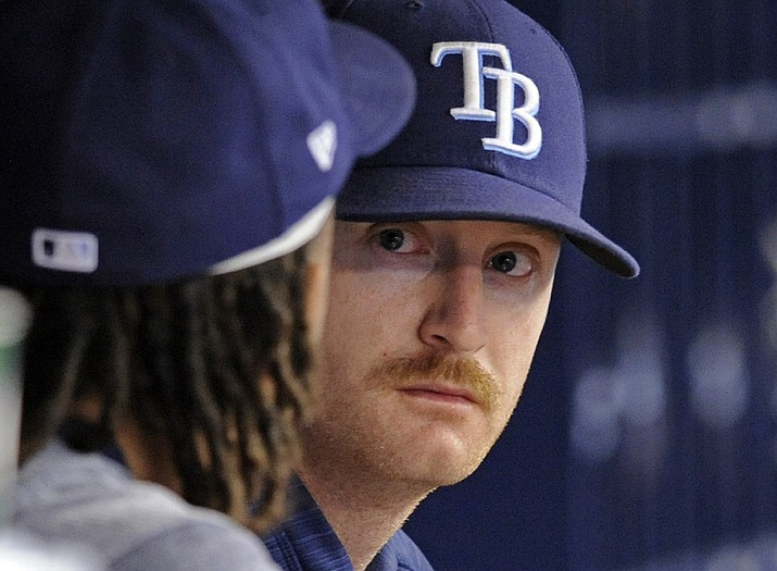 In this Oct. 1, 2017, file photo, Tampa Bay Rays pitchers Chris Archer, left, and Alex Cobb, right, talk in the dugout during the fifth inning of a baseball game against the Baltimore Orioles, in St. Petersburg, Fla. In a historically slow market, players and management are feuding publicly about riches and rules, and teams seemingly are seeking bargains like shoppers awaiting a closeout. Job-seekers include pitchers Alex Cobb and Lance Lynn; reliever Greg Holland; infielder Eduardo Nunez; outfielders Carlos Gomez and Carlos Gonzalez; and catcher Jonathan Lucroy. (Steve Nesius/AP, File)