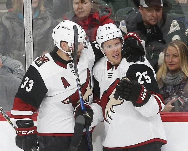 Arizona Coyotes' Alex Goligoski, left, congratulates Arizona Coyotes' Nick Cousins, right, on Cousins' goal off Minnesota Wild goalie Devan Dubnyk in the second period Thursday, Feb. 8, 2018, in St. Paul, Minn. (Jim Mone/AP)
