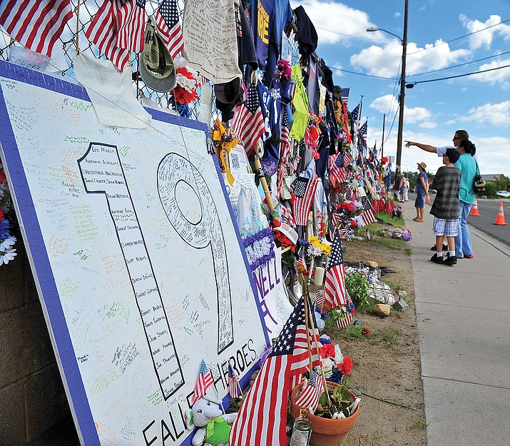 People pay their respects to the fallen 19 Granite Mountain Hotshots at the make shift memorial at Prescott Fire's Station 7 on Sixth Street in 2013.