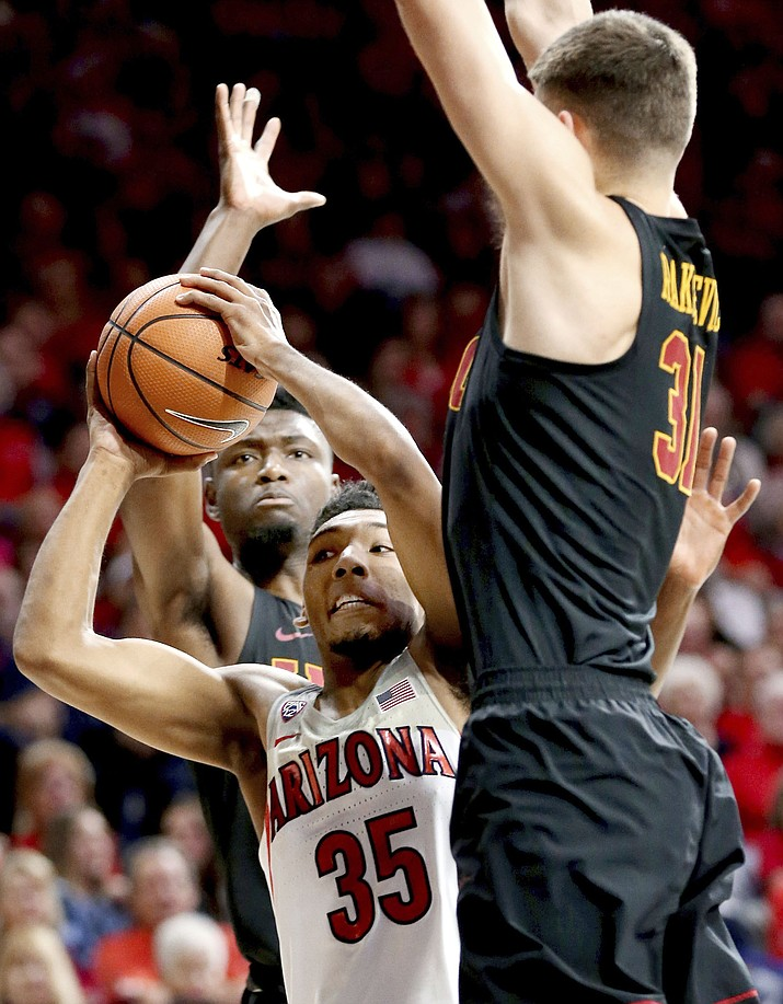 Arizona guard Allonzo Trier (35) looks for room to get off a shot between Southern California forward Chimezie Metu, left, and forward Nick Rakocevic during the first half of an NCAA college basketball game Saturday, Feb. 10, 2018, in Tucson.