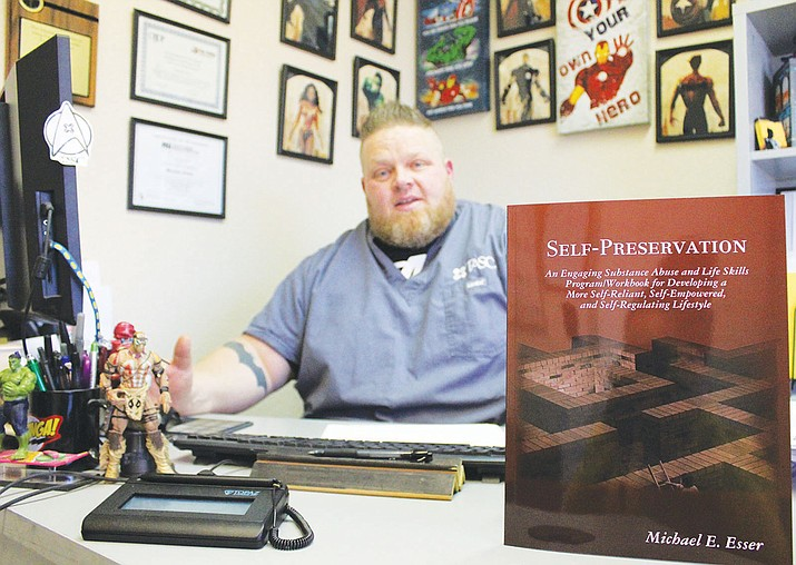 Michael Esser in his office surrounded everyday by superheroes, talks about the cover of his book, Self-Preservation.