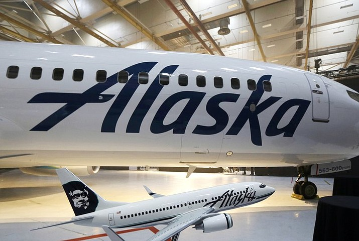 This Jan. 25, 2016, file photo, the new logo of Alaska Airlines is shown next to a model of a plane with the old livery in Seattle. An Alaska Airlines flight to Seattle was forced to return to Anchorage, Alaska, early Wednesday, Feb. 7, 2018, after a passenger locked himself in the bathroom, took off all his clothes, and refused to follow crew instructions. (AP Photo/Ted S. Warren)