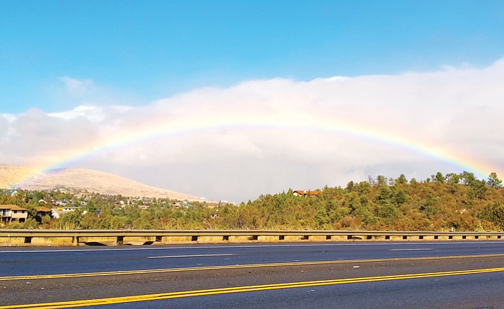 Local resident Kathi Buss takes a photo of the rainbow over Prescott Valley from Highway 69 near Costco after a storm moved through the area Monday, Feb. 12, 2018.