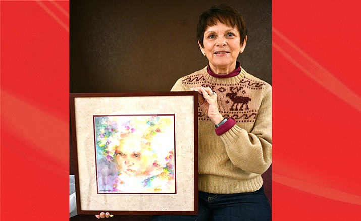 Deborah Gallagher poses with her painting titled 