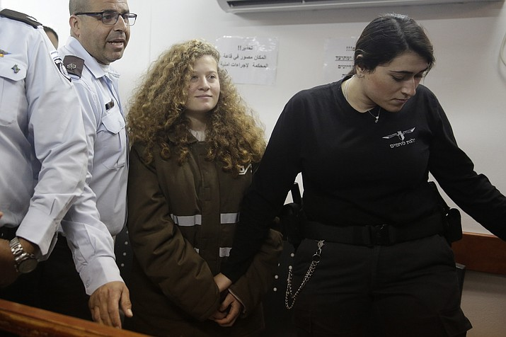 In this Jan. 15, 2018 file photo, Ahed Tamimi is brought to a courtroom inside the Ofer military prison near Jerusalem. Tamimi is to go on trial Tuesday, Feb. 13, 2018, before an Israeli military court, for slapping and punching two Israeli soldiers in December. Palestinians say her actions embody their David vs. Goliath struggle against a brutal military occupation, while Israel portrays them as a staged provocation meant to embarrass its military. Tamimi is one of an estimated 350 Palestinian minors in Israeli jails. (AP Photo/Mahmoud Illean, File)