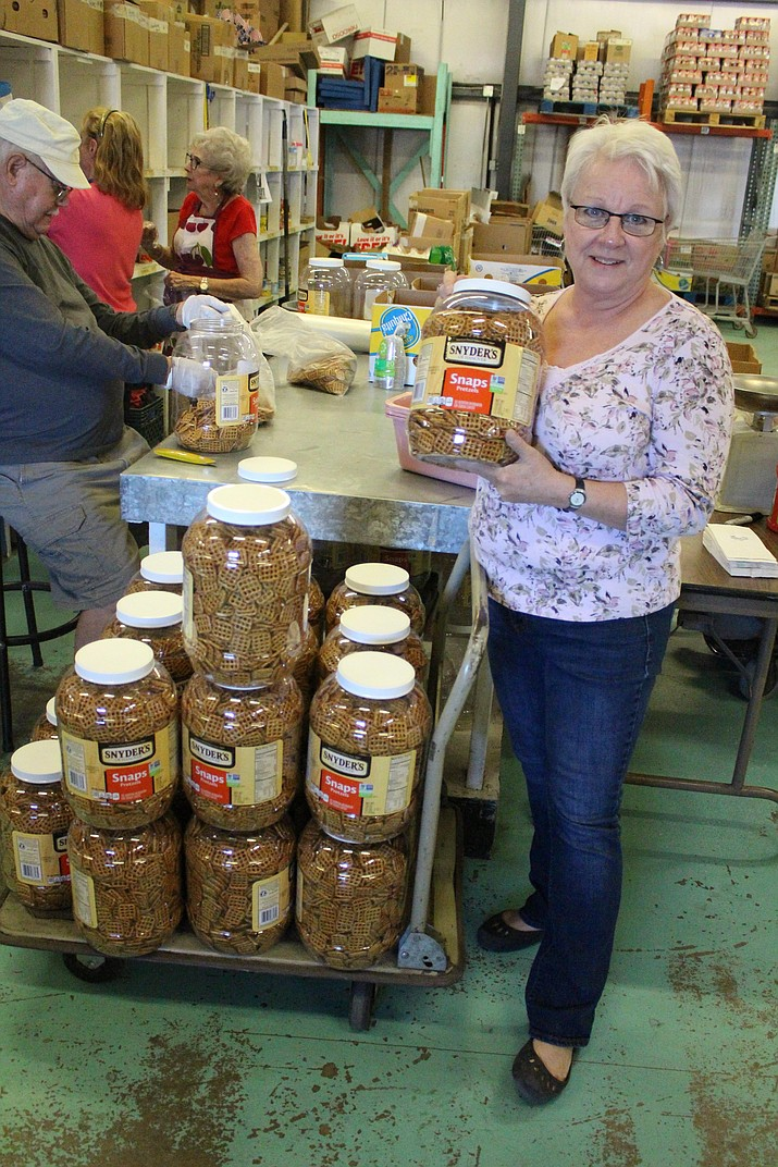 Kingman Area Food Bank Executive Director Catherine Walker shows a jar of pretzels. The food bank distributed food to about 104,000 people last year.