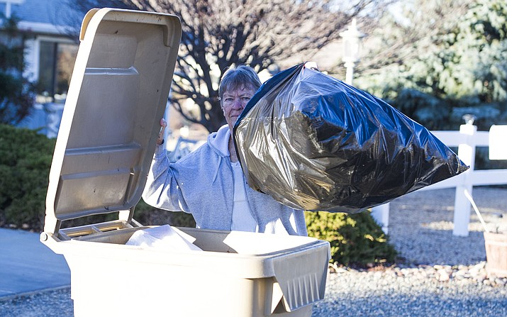 Mary Dyke puts trash in her garbage can Thursday, Feb. 8, 2018, in Prescott Valley. (Les Stukenberg/Courier)