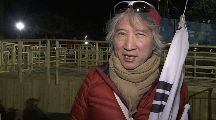 """In this image taken from video on Monday, Feb. 12, 2018, at the Pyeongchang Olympics in Pyeongchang, South Korea, South Korean Olympic fan Hong Seong-hun responds to the question: If you had the chance, what would you ask a North Korean? The pipe organ designer, said he didn't know there would be a joint North-South team when he reserved the ice hockey tickets. He said the flurry of diplomacy and conciliatory measures between the Koreas over the North's participation in the Olympics made him """"giddy like I am a child again."""" (AP Video)"""