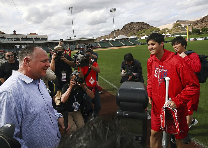 Los Angeles Angels' Shohei Ohtani, second from right holding bat, speaks with coach Mike Scioscia during a spring training baseball practice on Tuesday, Feb. 13, 2018, in Tempe. (Ben Margot/AP)
