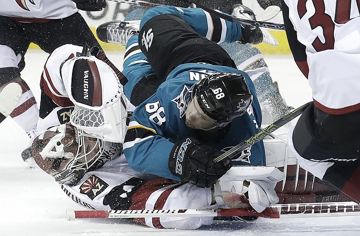 San Jose Sharks right wing Melker Karlsson, from Sweden, top, crashes into Arizona Coyotes goaltender Scott Wedgewood during the second period Tuesday, Feb. 13, 2018, in San Jose, Calif. (Jeff Chiu/AP)