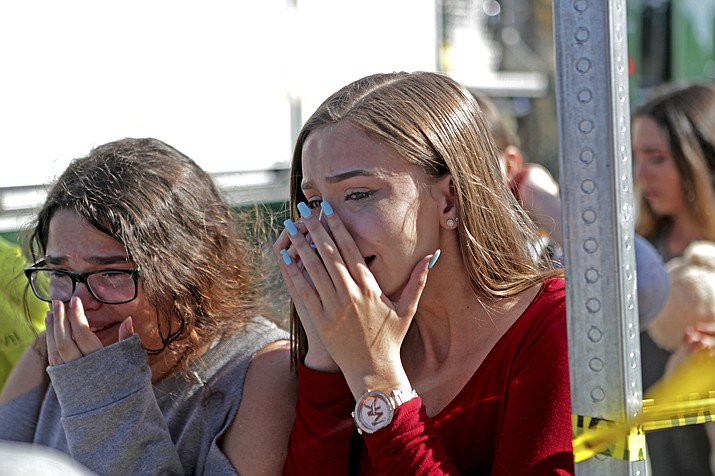 Students released from a lockdown are overcome with emotion following a shooting at Marjory Stoneman Douglas High School in Parkland, Fla., Wednesday, Feb. 14, 2018. (John McCall/South Florida Sun-Sentinel via AP)