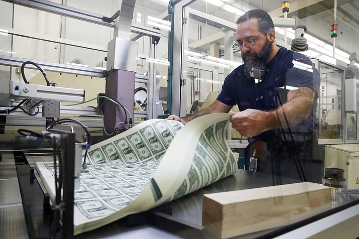In this Nov. 15, 2017, file photo, Vincent Tacconelli aerates printed sheets of dollar bills, the first currency notes to bear the signatures of Treasury Secretary Steven Mnuchin and Treasurer Jovita Carranza at the Bureau of Engraving and Printing in Washington. Most economists expect inflation to edge up and end the year a few tenths of a percentage point above the Federal Reserve's target. But most foresee only minimal effect on the economy. (AP Photo/Jacquelyn Martin, File)