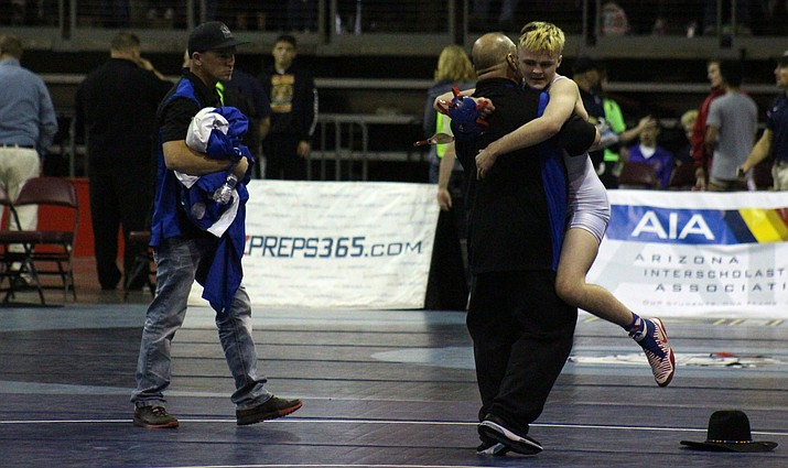 Camp Verde sophomore Korben Uhler (52-0) hugs assistant wrestling coach Mario Chagolla after he won his second straight state championship.  (VVN/James Kelley)