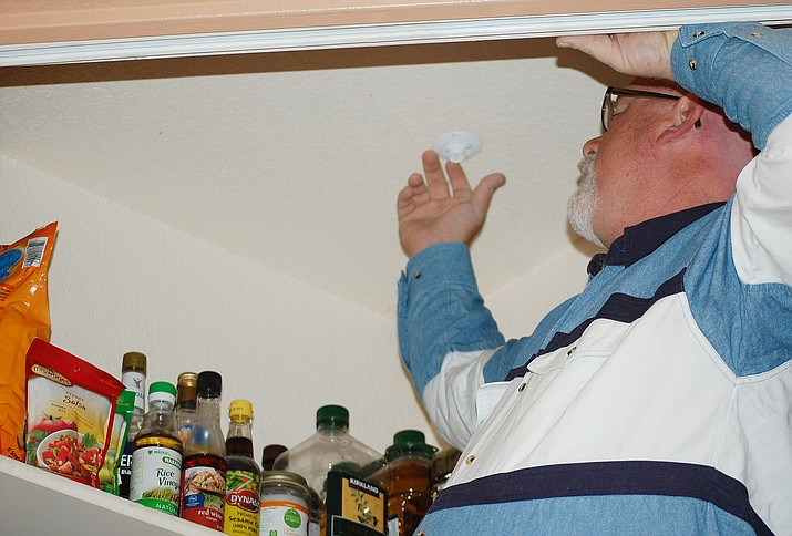The Courier's senior editor, Tim Wiederaenders, checks a fire sprinkler head in a home's pantry area. The installation is more easily done when the home is built, and each room — as well as all closets large enough to walk into — is required to have a sprinkler head. (Tracy Wiederaenders/Courtesy)