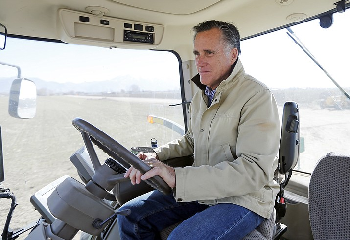 Former Republican presidential candidate Mitt Romney sits behind the wheel of a tractor during a tour of Gibson's Green Acres Dairy Friday, Feb. 16, 2018, in Ogden, Utah. The 2012 Republican presidential candidate plans to bid for the seat being vacated by retiring seven-term Utah Sen. Orrin Hatch. (AP Photo/Rick Bowmer)