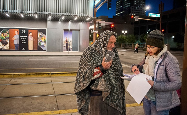 Anne Scott, right, a human services planner with the Maricopa Association of Governments, conducts a survey with Johnny McMillan, 50, who said he has been homeless, off and on, since he was 18.
