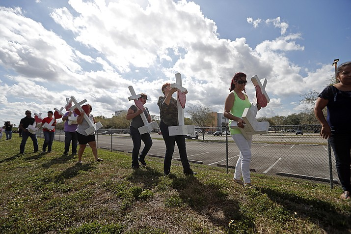 Volunteers help carry 17 crosses to be placed outside the Marjory Stoneman Douglas High School in Parkland, Fla., Sunday, Feb. 18, 2018, where 17 people were killed in a mass shooting on Wednesday. Nikolas Cruz, a former student, was charged with 17 counts of premeditated murder. (AP Photo/Gerald Herbert)