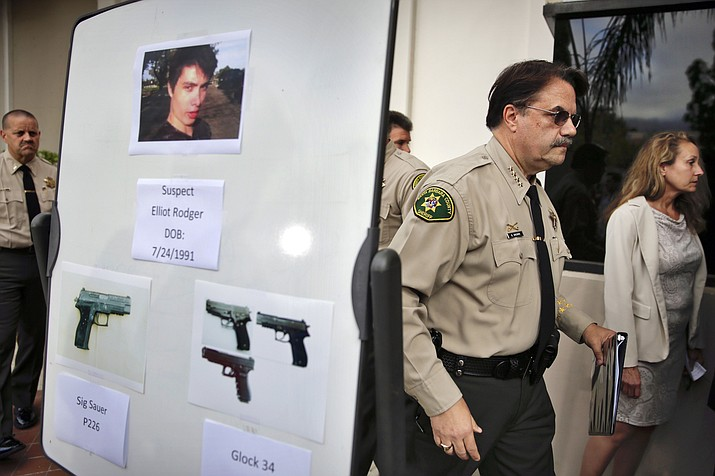 In this May 24, 2014 file photo, Santa Barbara County Sheriff Bill Brown, right, walks past a board displaying photos of gunman Elliot Rodger and the weapons he used in a mass shooting in Isla Vista, Calif., after a news conference in Santa Barbara, Calif. A growing number of states have passed laws or are considering bills allowing courts to temporarily remove guns from individuals deemed a danger to themselves or others, an intervention that advocates say stops shootings and suicides by disturbed individuals. (AP Photo/Jae C. Hong, File)