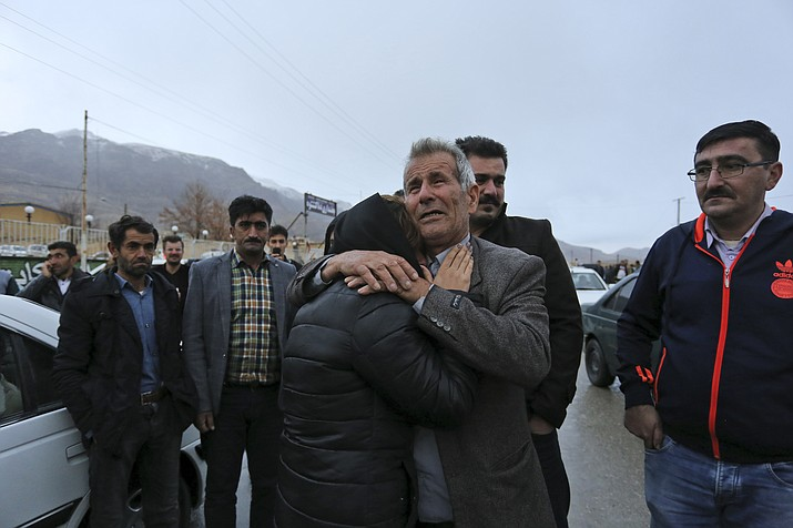 In this photo provided by Tasnim News Agency, family members of a plane crash victims weep in the village of Bideh, at the area that the plane crashed, southern Iran, Sunday, Feb. 18, 2018. An Iranian commercial plane crashed Sunday in a foggy, mountainous region of southern Iran, and officials said they feared all people aboard were killed. (Ali Khodaei/Tasnim News Agency via AP)