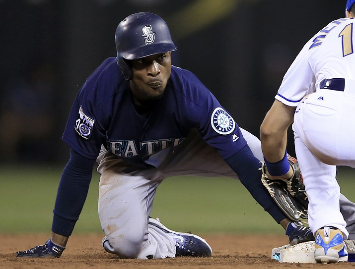 Seattle Mariners' Jarrod Dyson, left, beats the tag by Kansas City Royals second baseman Whit Merrifield on Aug. 4, 2017, in Kansas City, Mo. Dyson signed a two-year, $7.5 million contract with the Arizona Diamondbacks on Monday, Feb. 19, 2018. (Orlin Wagner/AP, File)