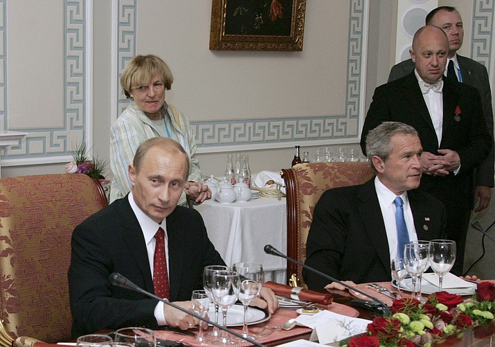 """In this Monday, July 19, 2006 file photo, Russian President Vladimir Putin, left, and U.S. President George W Bush attend a working dinner with the other leaders of the G8 nations, as Russian businessman Yevgeny Prigozhin stands on the right, in St. Petersburg, Russia. While Russian officials have denigrated a U.S. indictment charging 13 Russians with meddling in the 2016 U.S. presidential vote through an elaborate social media campaign, former Internet trolls employed at the same facility see them as well-grounded. The indictment alleged that Yevgeny Prigozhin _ a wealthy entrepreneur and restaurateur dubbed """"Putin's chef"""" _ funneled money to set up the troll factory that sent operatives to the United States, created fictitious social media accounts and used them to spread tendentious messages. (Sergei Zhukov, Sputnik, Kremlin Pool Photo)"""