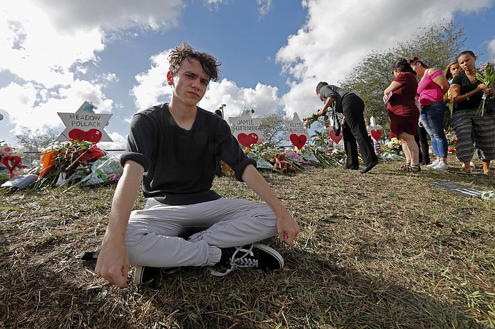 Chris Grady, a student at Marjory Stoneman Douglas High School, poses at a memorial outside the school, for Wednesday's mass shooting, in Parkland, Fla., Monday, Feb. 19, 2018. Grady huddled in his classroom at the high school last Wednesday listening to shots ring out nearby, what he felt wasn't fear, but anger. Grady and his friend are among about 100 Stoneman Douglas students who are heading to Florida's capital, Tallahassee, to push lawmakers to do something to stop gun violence. (AP Photo/Gerald Herbert)