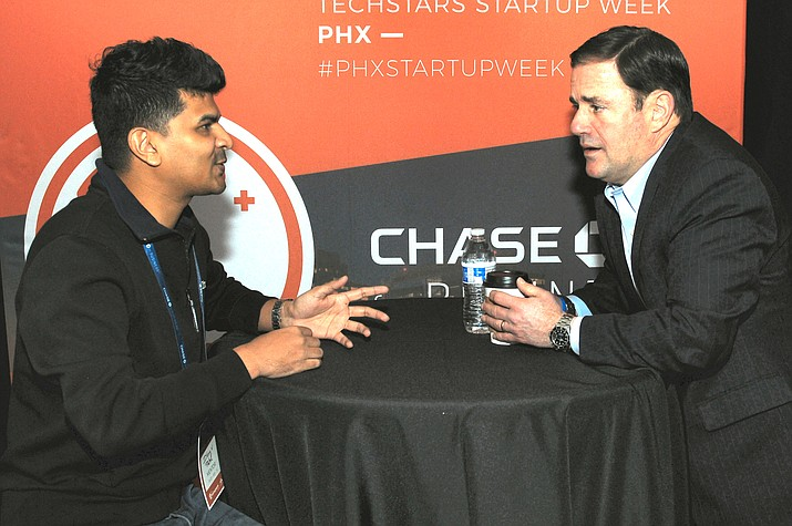 "Gov. Doug Ducey does some ""mentoring"" of Dhruv Patel Tuesday at an event for entrepreneurs. Patel is the owner of a new firm that helps small businesses establish their own web sites. (Capitol Media Services photo by Howard Fischer)"