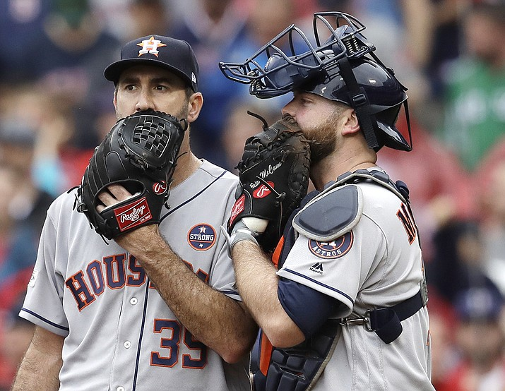 In this Oct. 9, 2017, file photo, Houston Astros relief pitcher Justin Verlander, left, and catcher Brian McCann talk during the fifth inning of Game 4 of baseball's American League Division Series against the Boston Red Sox in Boston. Major League Baseball is imposing stricter limits on mound visits in an effort to speed games but decided against 20-second pitch clocks for 2018. The new rules announced Monday, Feb. 19, 2018, include a general limit of six mound visits per nine-inning game without a pitching change, whether by a manager, coach or player. (Charles Krupa/AP, File)