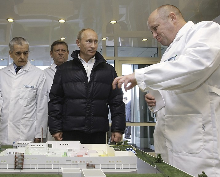 In this Monday, Sept. 20, 2010 file photo, businessman Yevgeny Prigozhin, right, shows Russian President Vladimir Putin, second right, around his factory which produces school means, outside St. Petersburg, Russia. On Friday Feb. 16, 2018, Yevgeny Prigozhin along with 12 other Russians and three Russian organizations, were charged by the U.S. government as part of a vast and wide-ranging effort to sway political opinion during the 2016 U.S. presidential election.(Alexei Druzhinin, Sputnik, Kremlin Pool Photo)