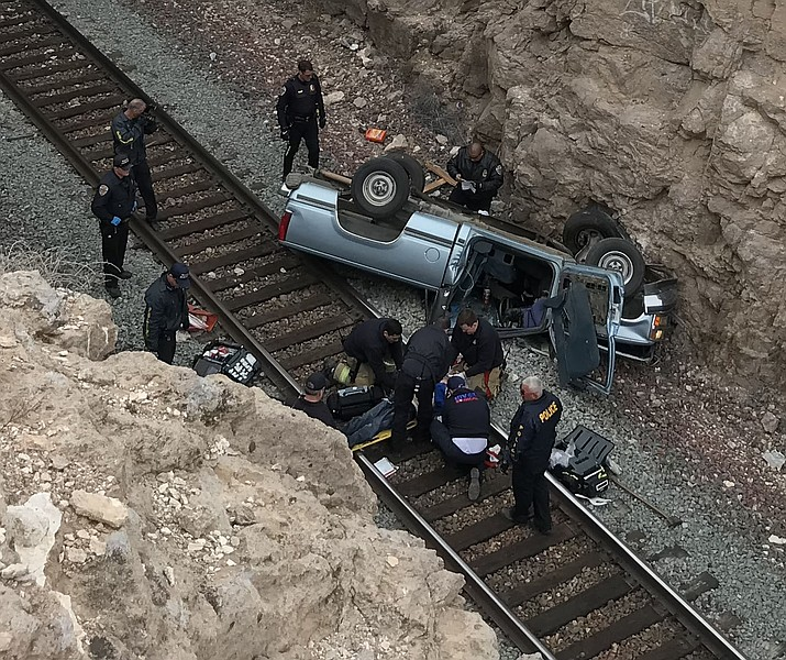 Jesus Carlos Contreras is attended to by emergency responders at the bottom of a canyon at the railroad overpass on Hualapai Mountain Road. Kingman Police Department investigators stated he drove off of the roadway, across a vacant lot before plummeting 70 feet. Contreras is now at University Medical Center in Las Vegas. (Kingman Police Department)