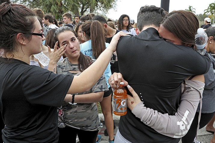 West Boca Raton Community High School students sophomore Leona Zaborsky, 16, right, and senior Julia Wheeler, 18, hug after reaching Marjory Stoneman Douglas High School in Parkland, Fla., Tuesday, Feb. 20, 2018. Hundreds of students walked out of the school Tuesday and made their way to the site of a school shooting about 10 miles (16 kilometers) away in a show of solidarity for bringing an end to gun violence. (Amy Beth Bennett/South Florida Sun-Sentinel via AP)