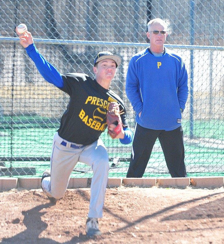 Prescott starting pitcher Jake Schulz warms up before practice Tuesday, Feb. 20, 2018, as head coach Kent Winslow looks on. Schulz is expected to be the No. 1 starter on the mound for the Badgers in 2018.