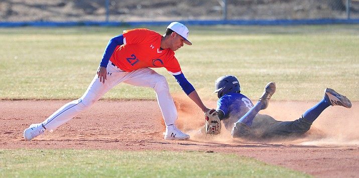 Chino Valley's Abdiel Sanchez tries to tag out a Lobo runner as the Cougars play the Snowflake Lobos to open the 2018 baseball season Thursday afternoon in Chino Valley. (Les Stukenberg/Courier)