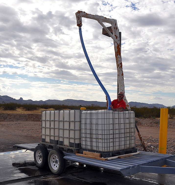 Golden Valley resident Michael Basile fills water cubes on his trailer at Golden Valley Improvement District's standpipe at Bolsa Drive and Estrella Road. Baisle, who hauls 812 gallons of water at a time, is one of the 454 residents who use the standpipe operation to fill their tanks.