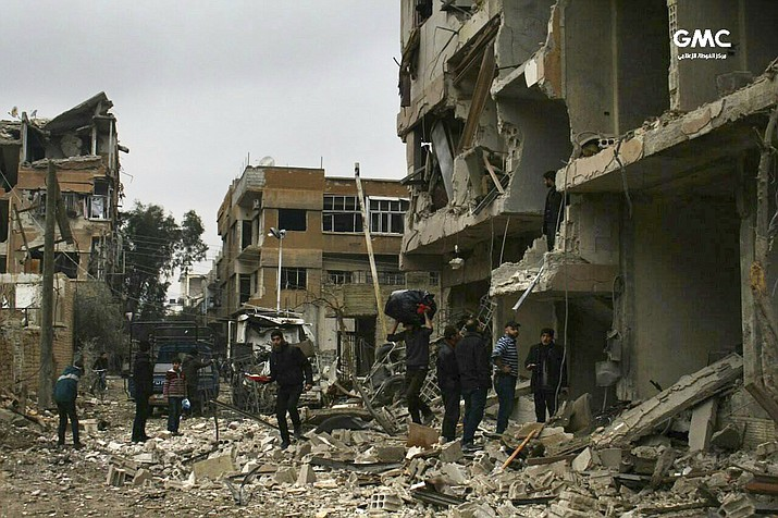 In this photo released on Thursday Feb. 22, 2018 which provided by the Syrian anti-government activist group Ghouta Media Center, which has been authenticated based on its contents and other AP reporting, shows Syrians check their destroyed buildings which attacked during airstrikes and shelling by Syrian government forces, in Ghouta, a suburb of Damascus, Syria. (Ghouta Media Center via AP)